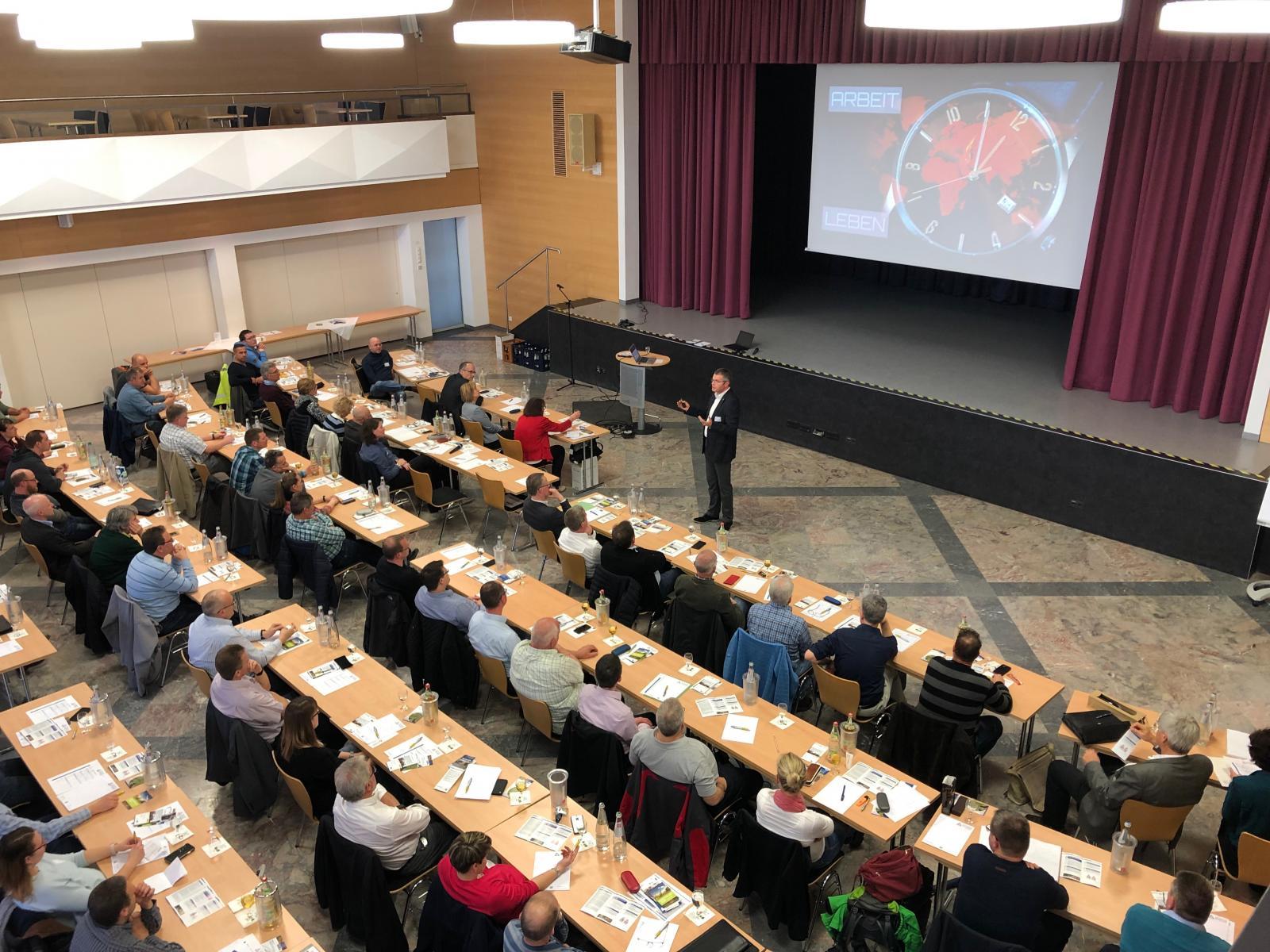 Vogelperspektive auf das Seminar (sitzende Teilnehmer und stehender Vortragender)